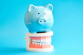 Cost of dental implants in Marshall represented by piggy bank atop model teeth