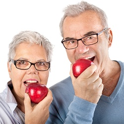 Older man and woman eating apples