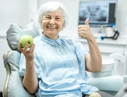 Senior dental patient enjoying benefits of implant-retained dentures