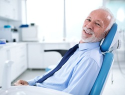 Male senior dental patient happy with his implant-retained dentures