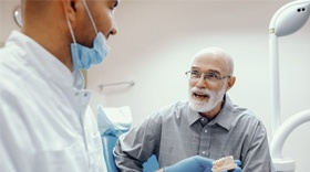 An older man talking to his dentist