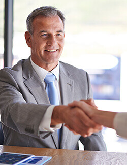man in business suit shaking hands with dentist