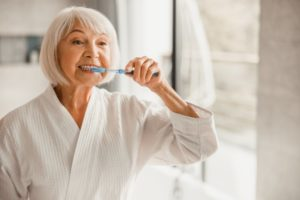 senior woman brushing teeth to protect oral health during quarantine