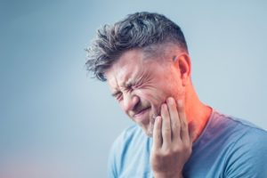 man with toothache, needs emergency dentistry during COVID-19