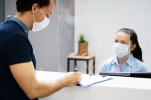 dental team member and patient wearing masks during check-in