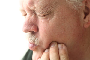 frowning senior man with untreated implant denture in Marshall