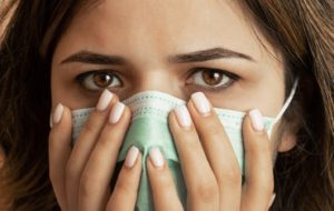 Woman wearing mask, surprised by facts about gum disease and COVID-19